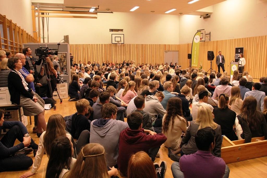 Full gymsal med stor stemning, journalister og simultantolk for internasjonale deltakere i buret til venstre.